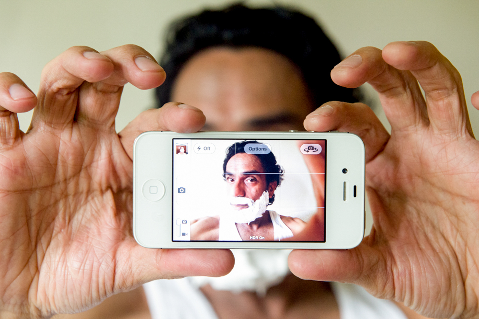 Portrait of man through a phone screen, with shaving cream on his face