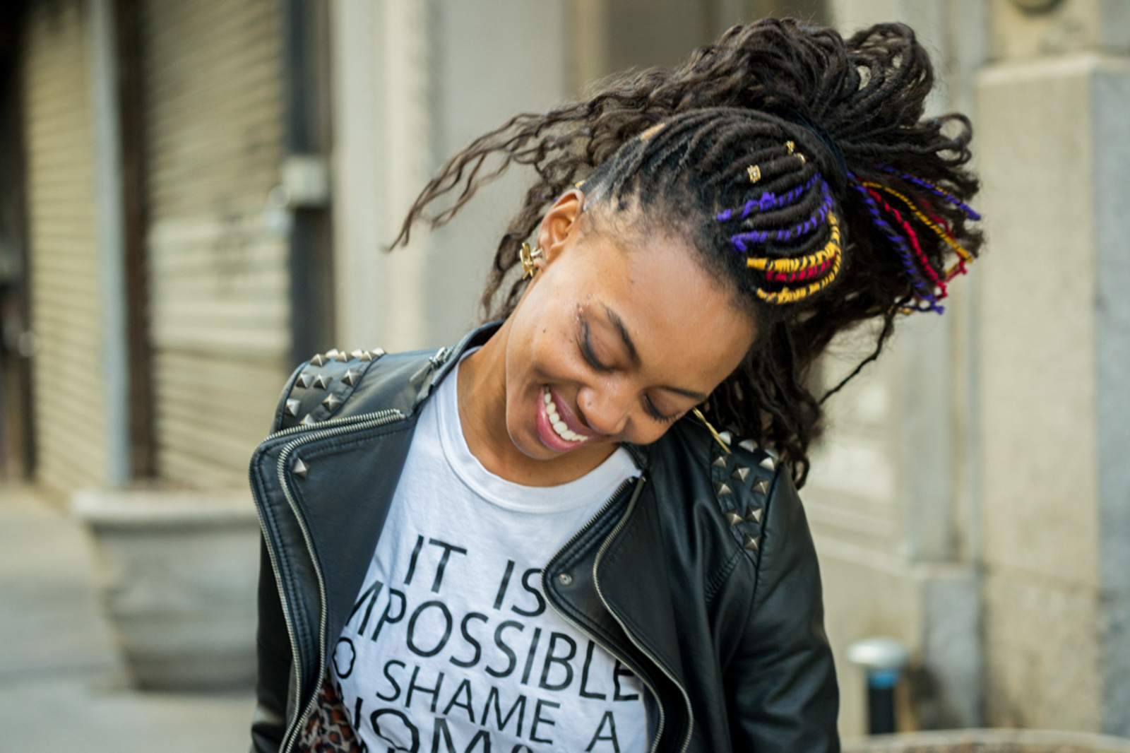 Portrait of woman with dreadlocks and leather jacket, smiling in motion
